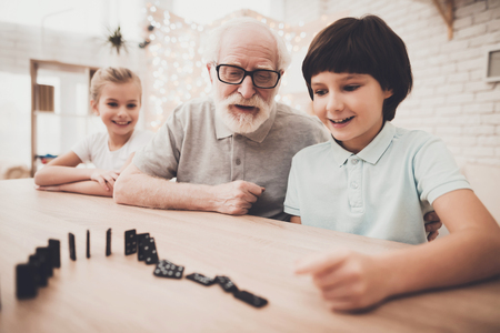 Grandfather, grandson and granddaughter at table at home. Grandpa and children are playing with blocks Standard-Bild - 98600795
