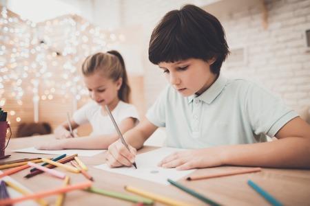 Kinderen aan tafel thuis. Broer en zus tekenen met kleurpotloden. Stockfoto