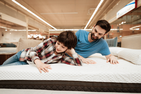 Handsome bearded father with young son is testing mattress for softness. Testing softness of mattress. Choosing mattress in store Reklamní fotografie