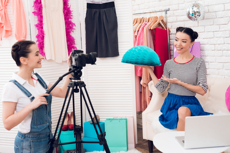 Two fashion blogger girls in jeans and shirt with skirt hold up colorful paper sphere with one girl behind camera.