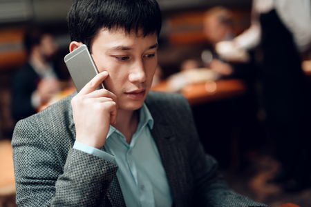 Meeting with chinese businessmen in suits in restaurant. Man is talking on his phone.
