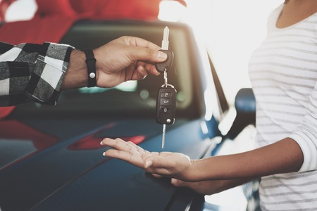 Close up man is giving keys to woman. African american family at car dealership. Father, mother and son near new blue car.