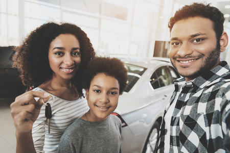 African american family at car dealership. Mother, father and son are taking selfie with keys for new grey car.