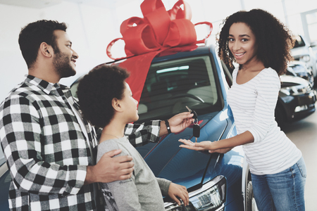 African american family at car dealership. Father, mother and son near new blue car. Man is presenting keys to woman. Stock Photo