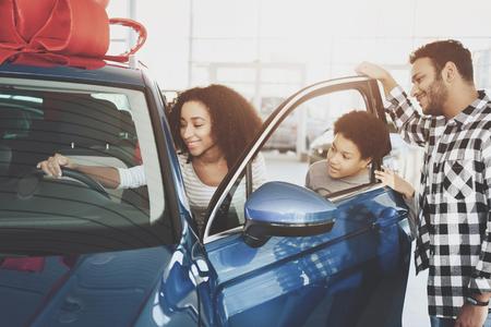 自動車販売店でアフリカ系アメリカ人の家族。新しい青い車の近くに父、母と息子。 写真素材 - 99714898