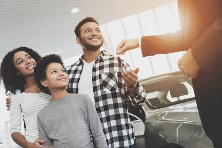 Afroamerykańska rodzina w salonie samochodowym. Sprzedawca wręcza kluczyki do nowego szarego auta. Zdjęcie Seryjne
