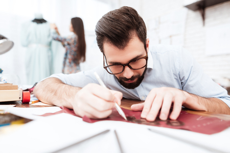 Two male and female fashion designers making cutout on leather.