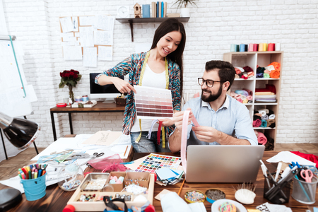 Two male and female fashion designers looking at color palette. Stock Photo