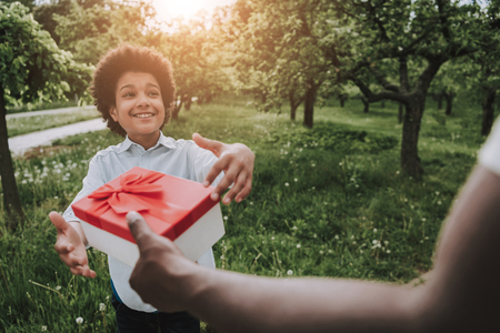 Father makes surprise to son in park. Present concept. Stock Photo