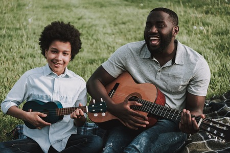 Father and son in park playing the guitar and singing. Parents and children relationship concept.