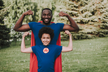 Father and son in park in suits of superheroes have fun. Parent and child relationship concept.