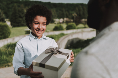 Son gives birthday gift to father. Father looks happy. Family relations. Celebration concept. 版權商用圖片