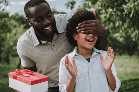 Father surprises son in park closing his eyes. Birthday present concept.
