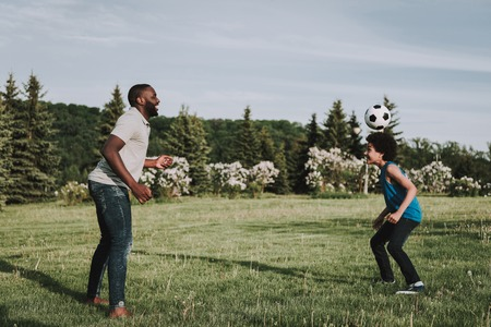 Father and son playing in the park with ball. Parent and child relationship concept.