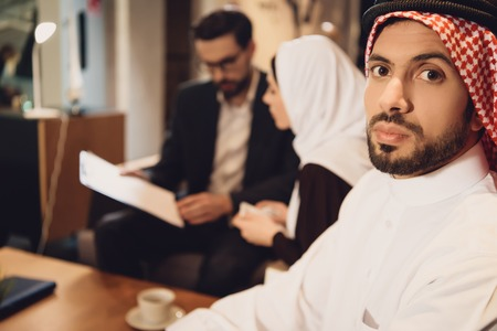 Discouraged Arab man with wife at psychologist reception. Family psychotherapy concept.