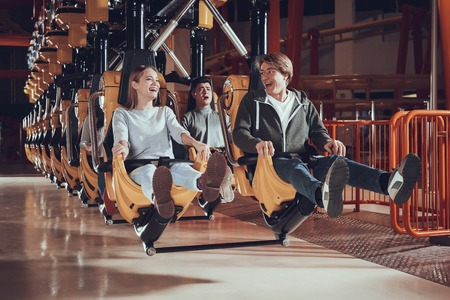 Young people raise their feet while sitting on the carousel. Cheerful friends smiling at each other in luna park. Stok Fotoğraf
