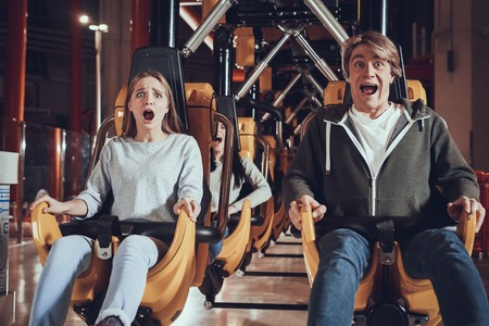 Unforgettable moments in amusement park. Young people are shocked by the speed of the carousel.