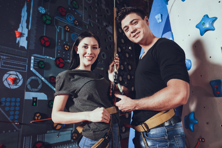 Guy with girl looks at camera. Friends getting ready for rock climbing.