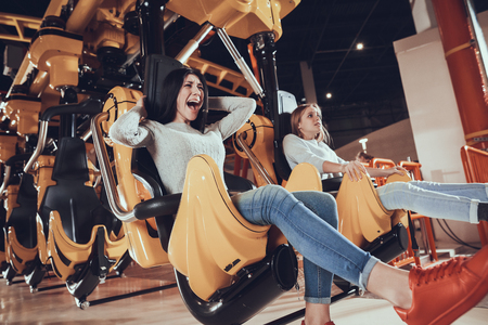 Picture of shocked excited two female friends sitting on carousel in amusement park.