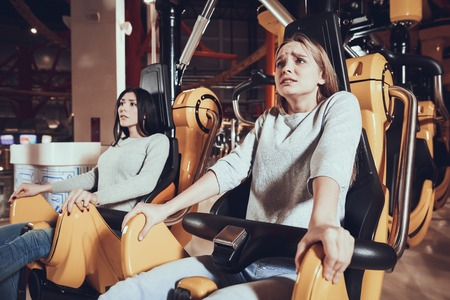 Close up portrait of two shocked girls on carousel in amusement park. Best friends are afraid of speed.