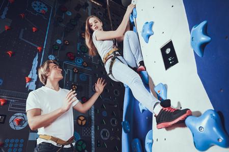 Boy insures the girl who climbs on the wall. Banco de Imagens - 102809916