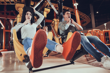 Youth entertainment in amusement park. Young friends, boys and girls in shocked. Extreme attraction at amusement park. Stok Fotoğraf