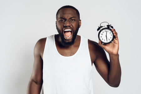 Angry African American man yells holding alarm clock. Morning awakening. Waking up. Isolated on white background. Studio portrait.
