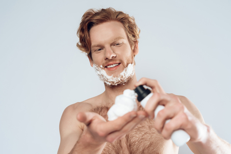 Young red haired guy applies shaving cream on palm of hand. Morning hygiene procedures. Isolated on grey background. Studio portrait.