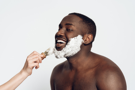 African American man smears shaving cream on face by shaving brush. Male hygiene. Isolated on white background. Studio portrait. Stock Photo
