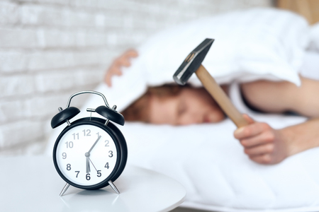 Young red haired man hammers alarm clock. Lack of sleep. Morning awakening. Waking up. Stock Photo