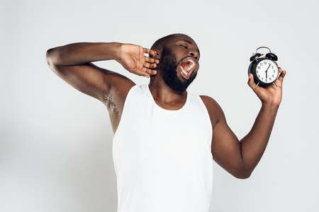 African American man yawns holding alarm clock. Guy slept through work. Isolated on white background. Studio portrait.