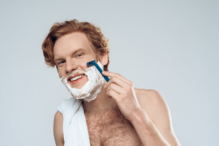 Young red haired guy neatly shaves with razor. Male hygiene. Morning hygiene procedures. Isolated on grey background. Studio portrait.