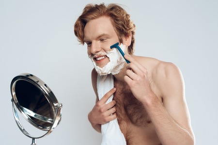 Young red haired guy is shaving with razor, looking in mirror. Male beauty concept. Male hygiene. Isolated on grey background. Studio portrait. 版權商用圖片