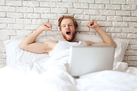 Red haired young businessman stretches in bed, browsing web pages. Yawn. Morning awakening.
