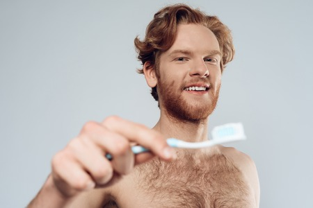 Red headed man is holding toothbrush with toothpaste. Male hygiene. Morning hygiene procedures. Isolated on grey background.