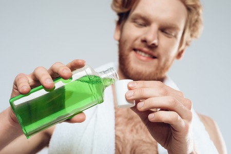 Top view. Red haired man pours mouthwash into cap. Morning hygiene procedures. Isolated on grey background. Studio portrait.