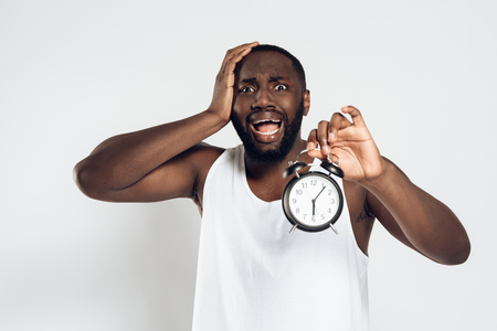African American man holds head with alarm clock in hand, overslept his work. Isolated on white background. Studio portrait.