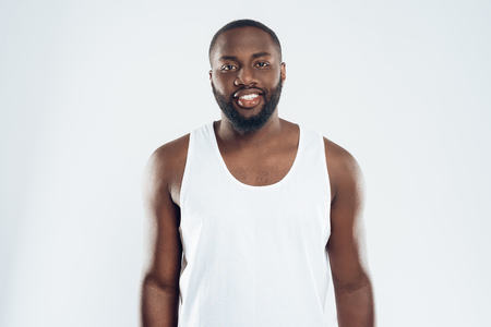 Portrait of African American smiling man in white singlet. Isolated on white background.