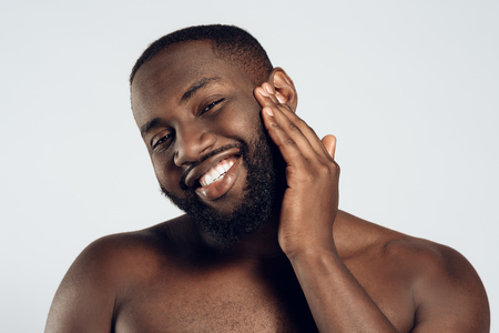 African American smiling man is smeared with face cream. Face care. Morning hygiene procedures. Isolated on white background. Studio portrait.