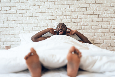 Happy awakened man is stretched out in bed. Early morning. Pleasant awakening. Waking up.