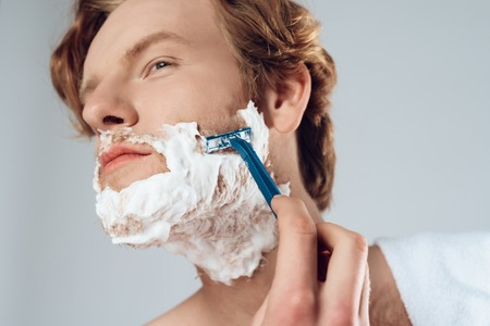 Close up. Young red haired guy neatly shaves with razor. Male hygiene. Isolated on grey background. Studio portrait.
