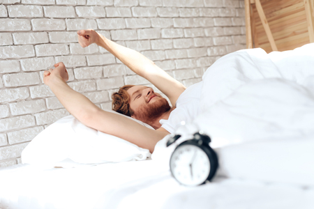 Young red haired man stretches out in bed. Morning awakening. Sweet dreams. Waking up. Healthy sleep.