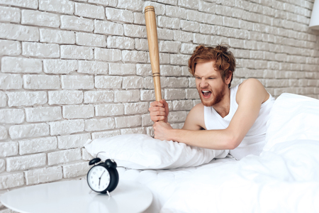 Red haired evil man swings baseball bat at alarm clock, which woke him. Lack of sleep. Morning awakening. 写真素材