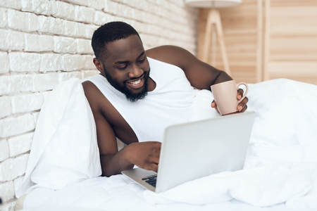 Black waking man drinks coffee in bed while working with laptop. Early morning. Pleasant awakening.