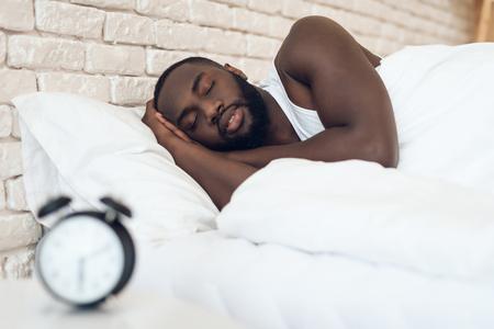 African American man sleeps in bed next to alarm clock. Healthy sleep. Sweet dreams.
