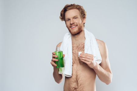 Red haired man is holding mouthwash. Morning hygiene procedures. Isolated on grey background. Studio portrait. 版權商用圖片