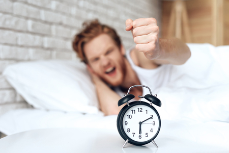 Young, irritated man reaches out to turn off ringing alarm clock.