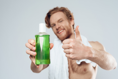 Red haired man posing with bottle of mouthwash and showing thumbs up. Care of teeth. Dental hygiene. Isolated on grey background. Studio portrait.