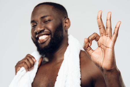 Smiling black man with white towel showing ok gesture. Morning hygiene procedures. Isolated on white background. Studio portrait.