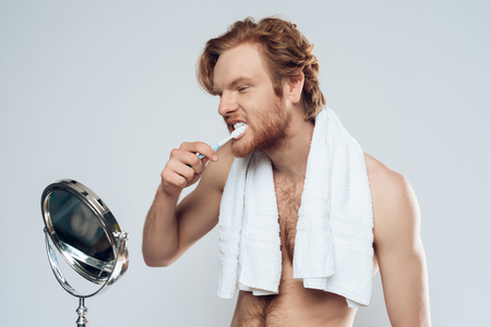 Red haired man is brushing teeth while looking in mirror. Healthy lifestyle. Morning hygiene procedures. Isolated on grey background.